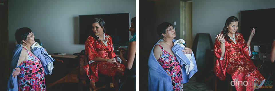mom sits by daughter bride as she prepares for her wedding