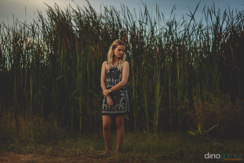 blonde bride stands among tall beach grass sugarcane in los cabo