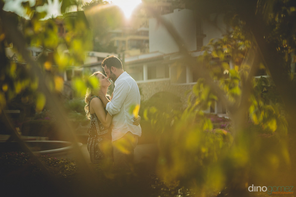 photo of newlyweds through trees at sunset in todos santos mexic