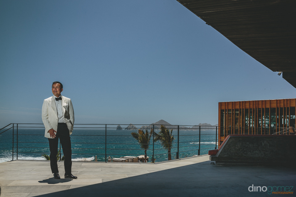 groom on wedding day stands in front of the arch in cabo san luc