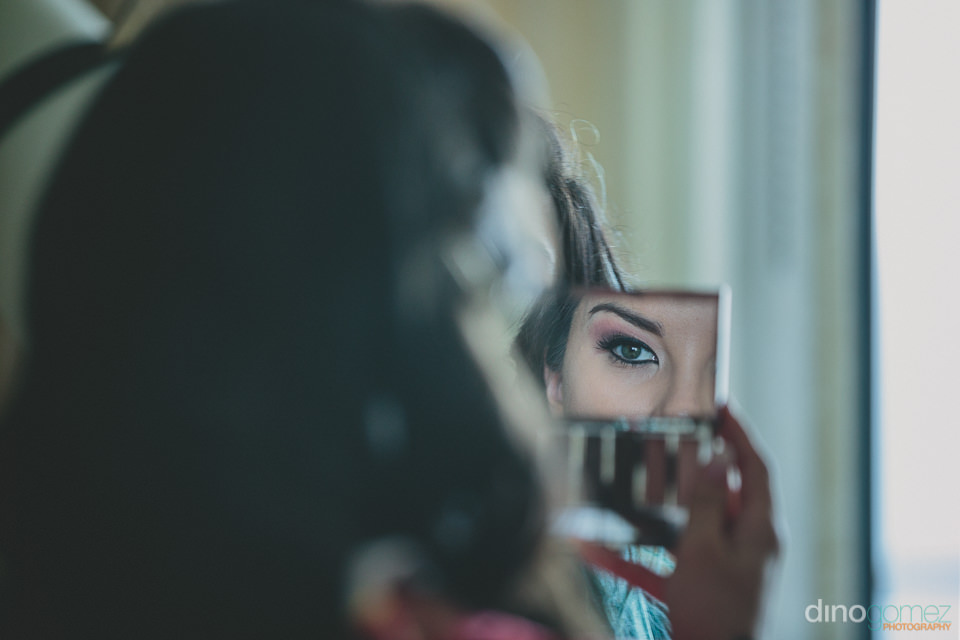 bride looks in mirror loves her wedding makeup