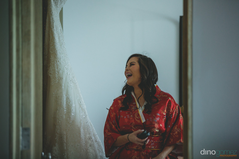 bride laughs and smiles while looking at wedding dress