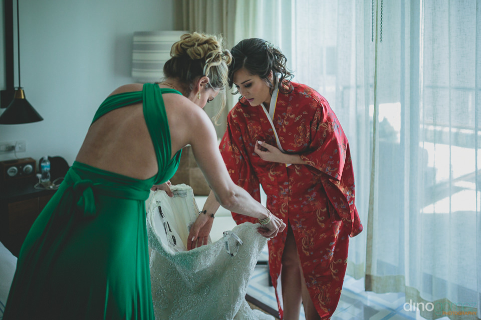maid of honor helps bride put on wedding dress