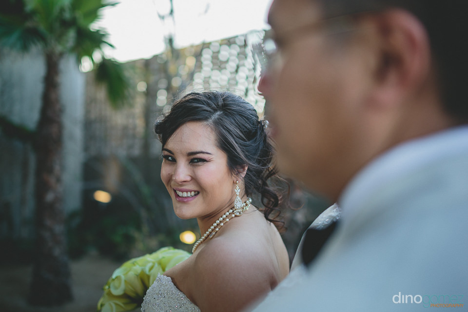 bride smiles at photographer dino gomez camera after wedding cer