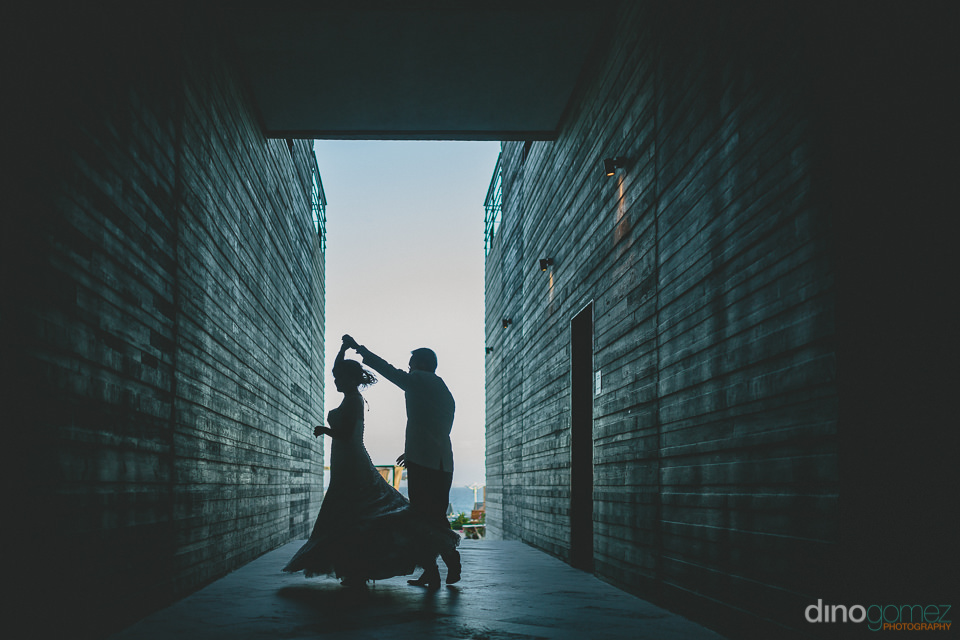 newlyweds dance on the rooftop of the cape hotel in cabo