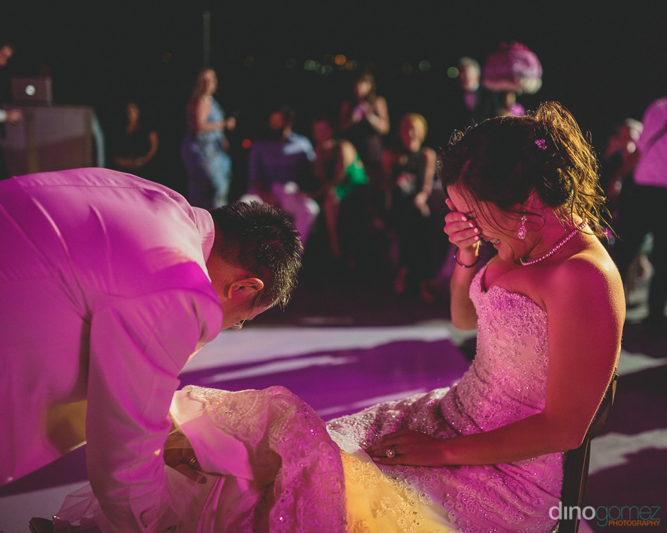 groom removes brides garter bride guests laugh
