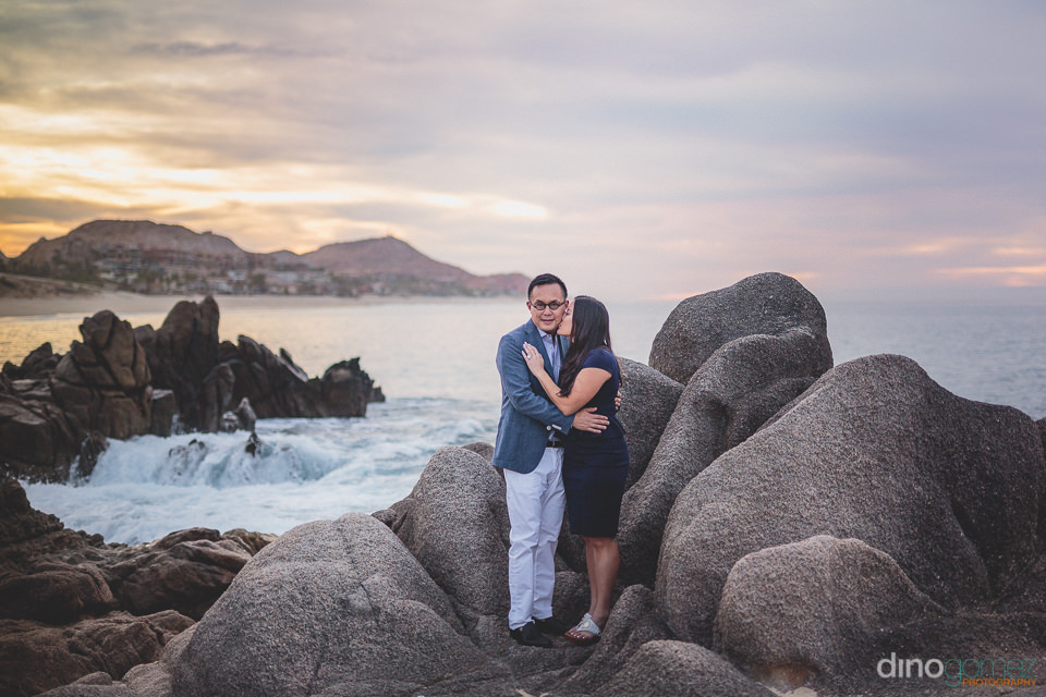 newlyweds hug and kiss standing on beach rocks in los cabos mexi