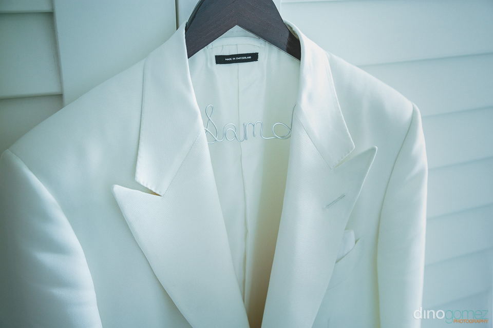 white designer wedding suit jacket worn by groom in mexico photo