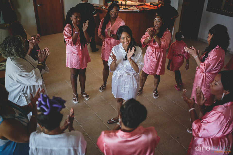 bridesmaids in pink robes cheer for the bride the morning of her