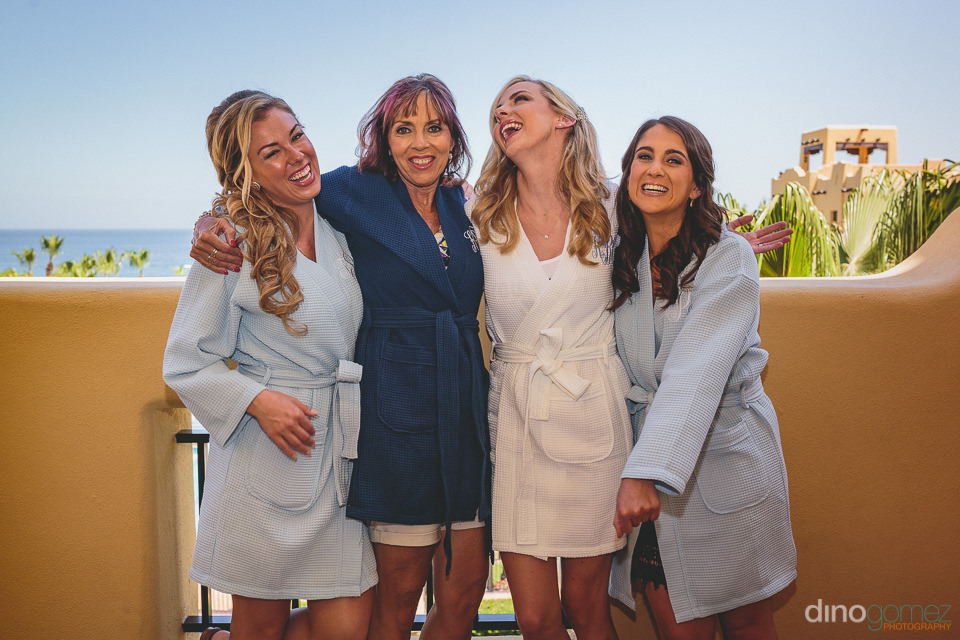 bride and bridesmaids stand on balcony of riu palace before dest