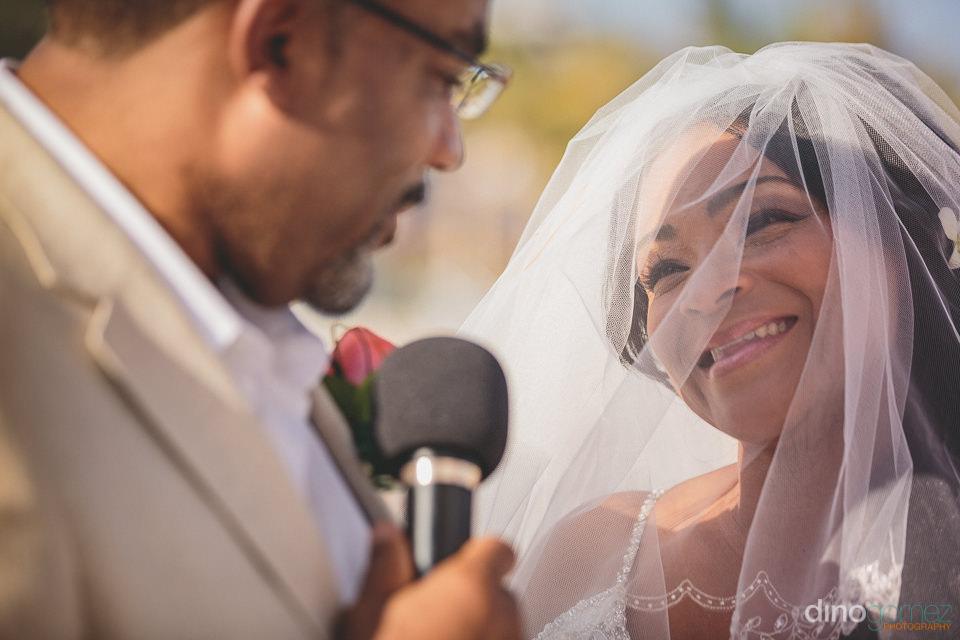 groom speaks to bride on microphone during destination wedding i