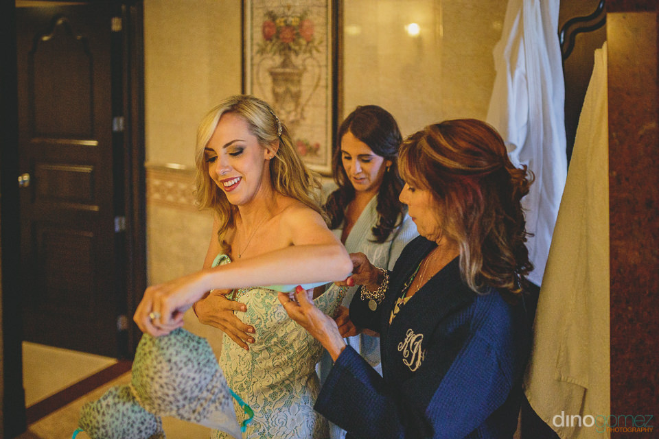 mother helps bride daughter into blue wedding dress before luxur
