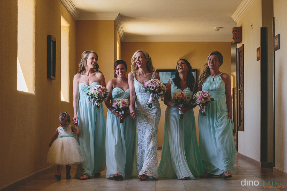 pretty bride bridesmaids smile and laugh as they walk to the cer