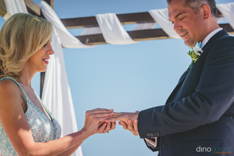 bride puts ring on groom at dream beach destination wedding