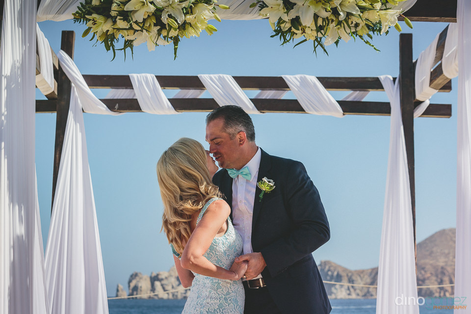 first kiss as husband and wife under chuppah on cabo beach