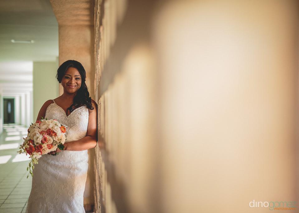 bride stands in sunny hallway in barcelo grand faro hotel