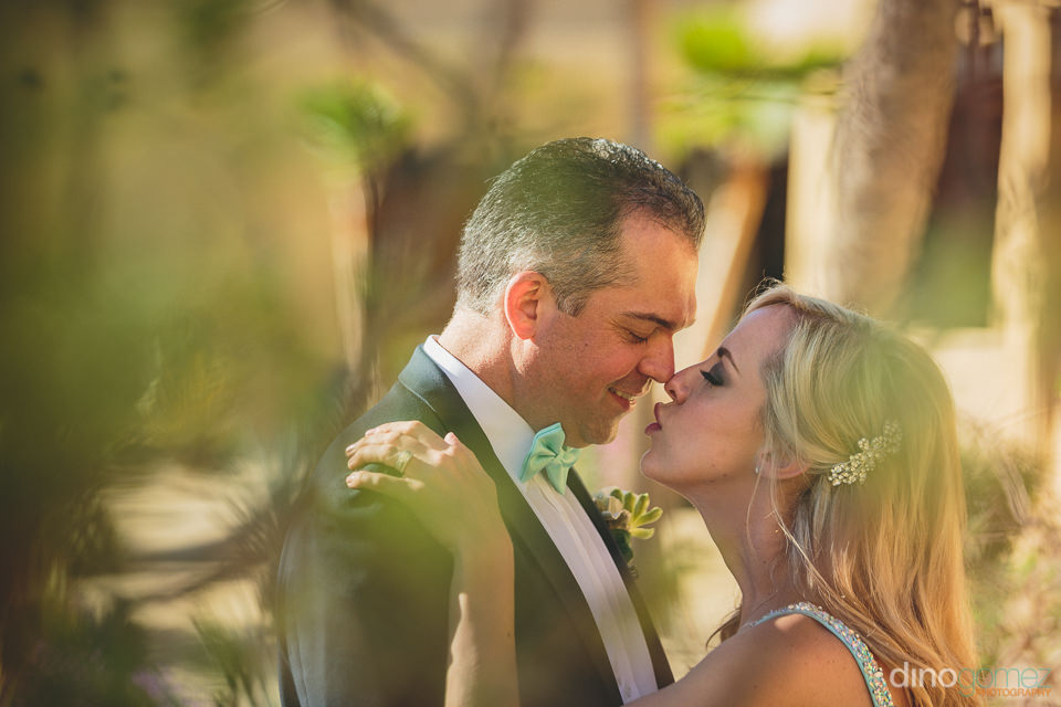 canadian and hong kong newlyweds kiss in cabo wedding photo by d
