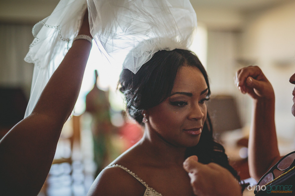 friends help bride put on wedding veil photos by dino gomez
