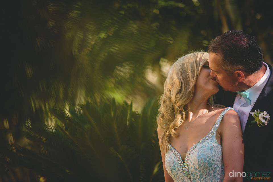 mesmerizing wedding photo of newlyweds in front of green forest