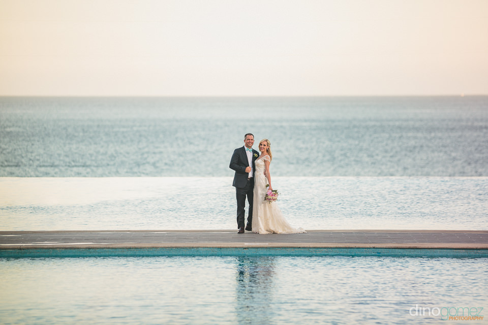 newlyweds in front of ocean and pool blue water cabo wedding pho