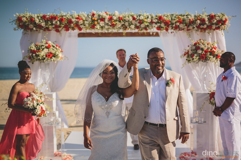 newlyweds walk hand in hand away from the wedding altar after be