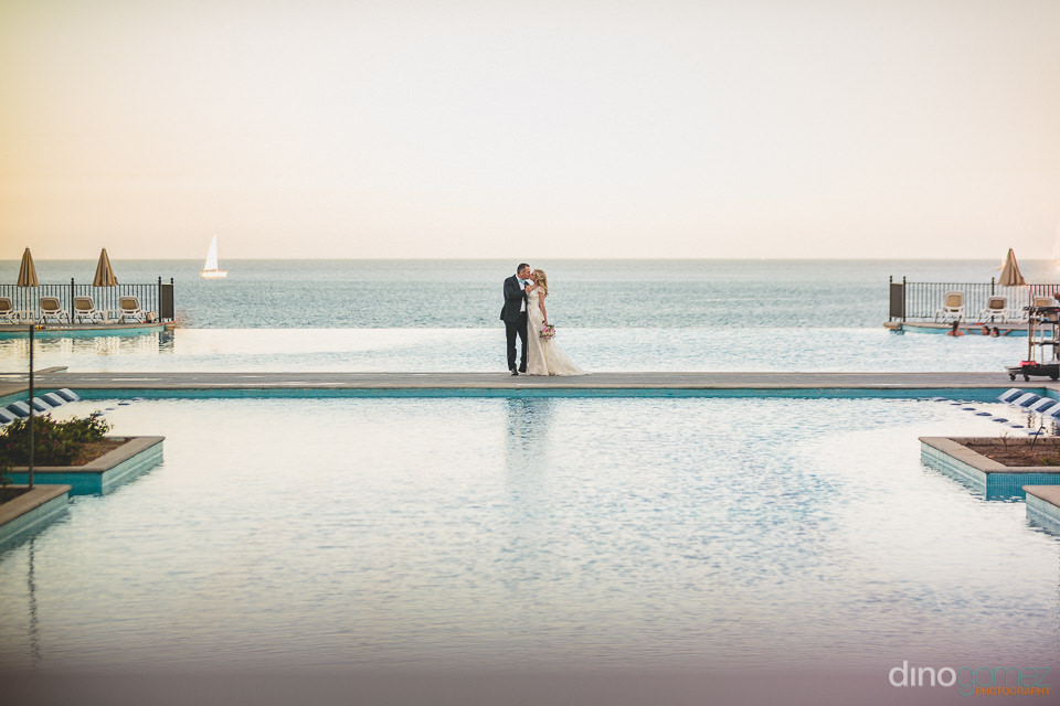 wedding photo newlyweds infinity pool blends into ocean
