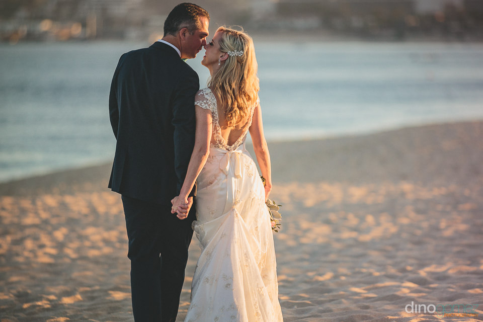 newlyweds walk on medano beach at sunset after wedding