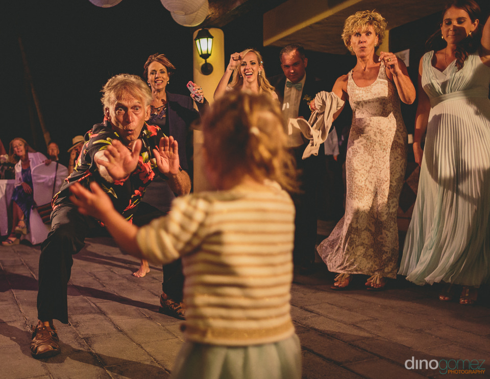 young and old wedding guests dance at wedding reception