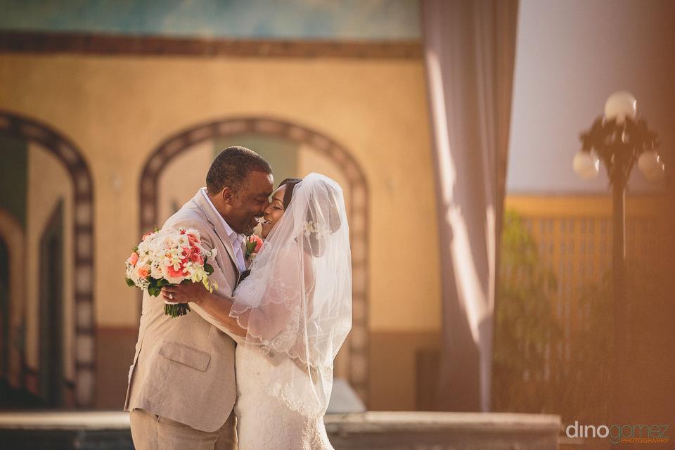 newlyweds laugh and kiss at destination wedding at barcelo grand