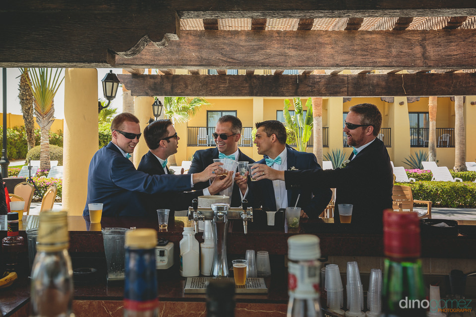 groom groomsmen have shot of tequila before cabo destination wed