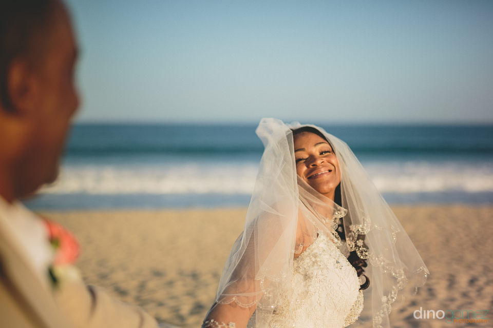 cabo beach wedding waves roll in as newlyweds walk by in photo b