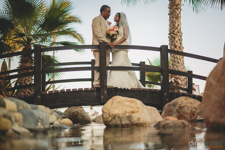 newlyweds bride groom stand on small bride walkway in mexico