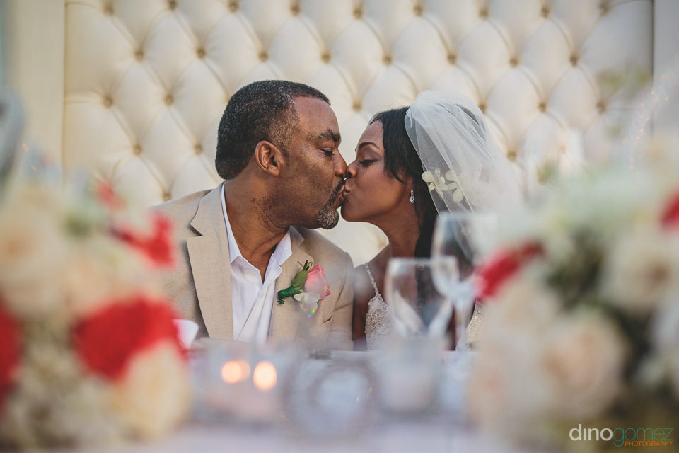 bride and groom kiss while seated at head table during dinner