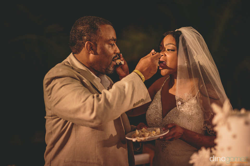 newlyweds give each other a bite of wedding cake at cabo wedding