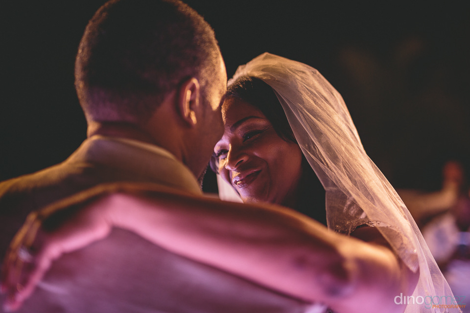 blissful bride smiles at her groom as they dance close