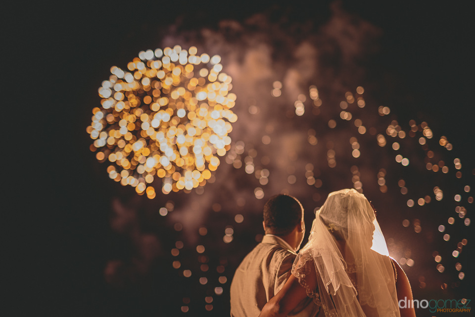 fireworks go off in the sky above the bride and groom