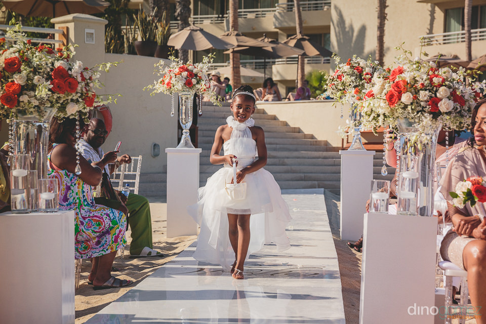 flower girl in white dress throws rose petals on wedding aisle