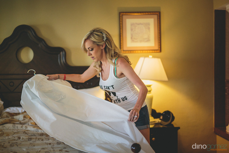 bride on morning of wedding takes out her wedding dres