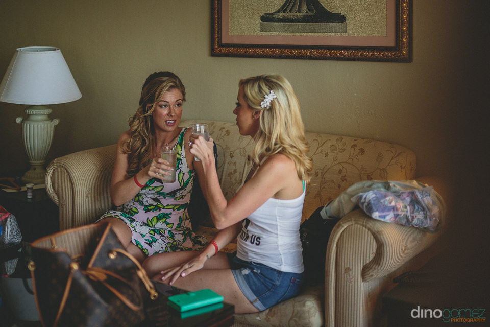 sisters sit and talk on couch before her wedding in cabo san luc