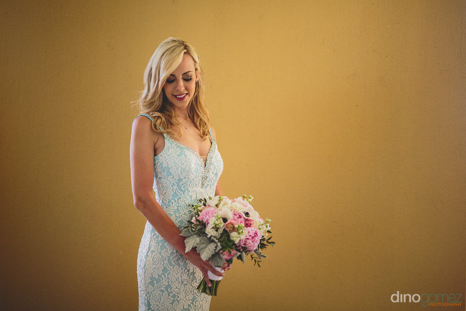 beautiful bride holds bouquet and poses for wedding photo by din