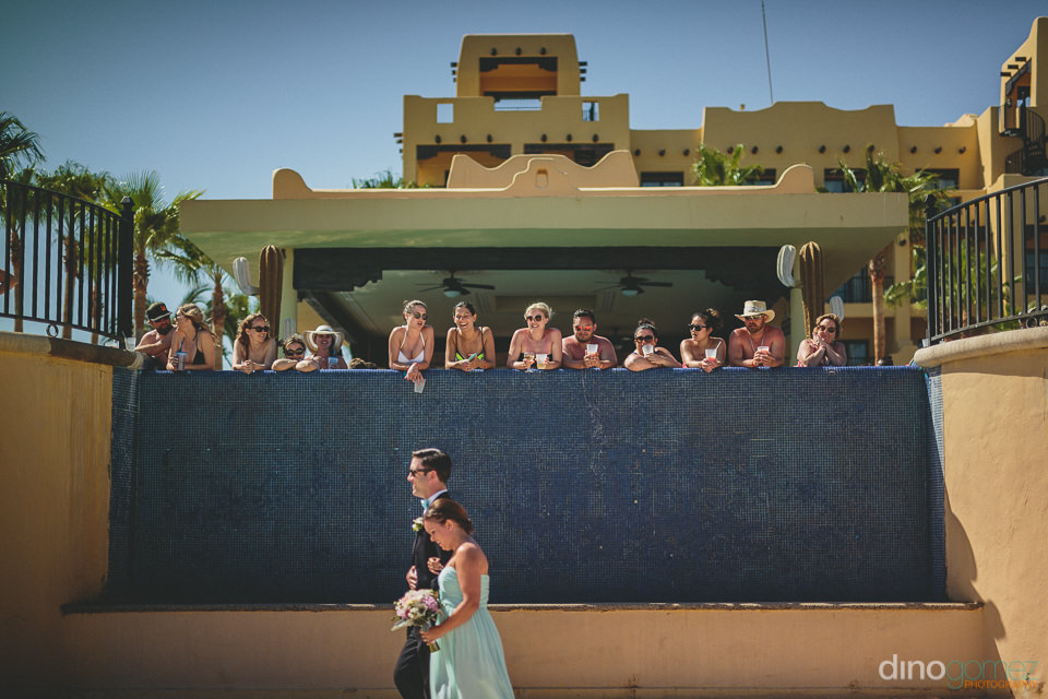 hotel guests watch wedding ceremony from pool at riu hotel