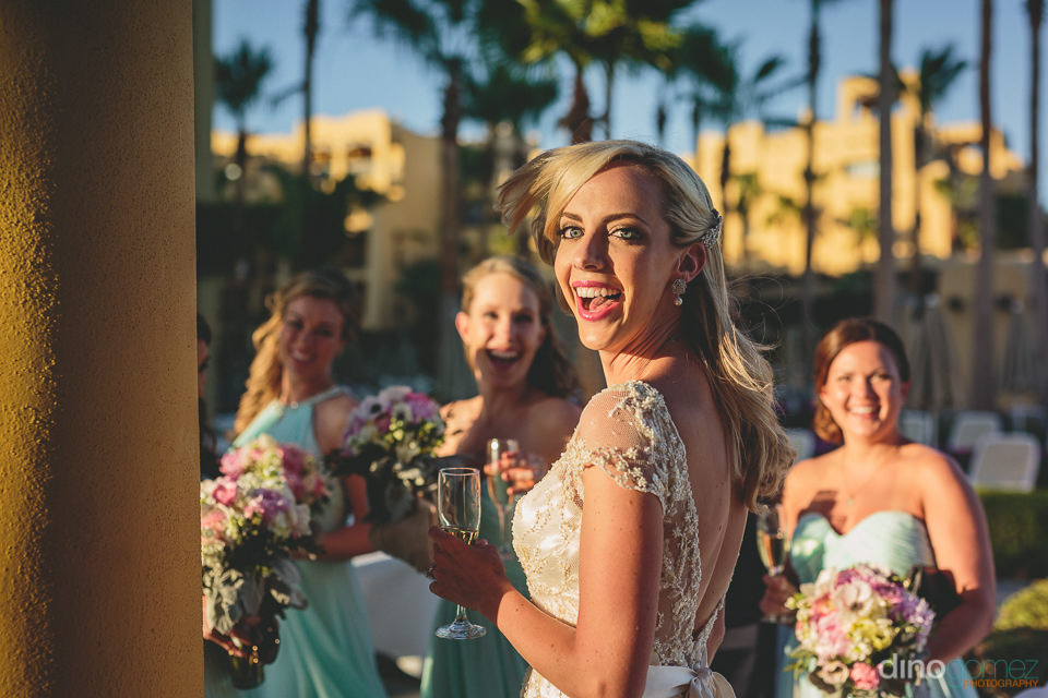 bride and bridesmaids drink champagne after wedding ceremony