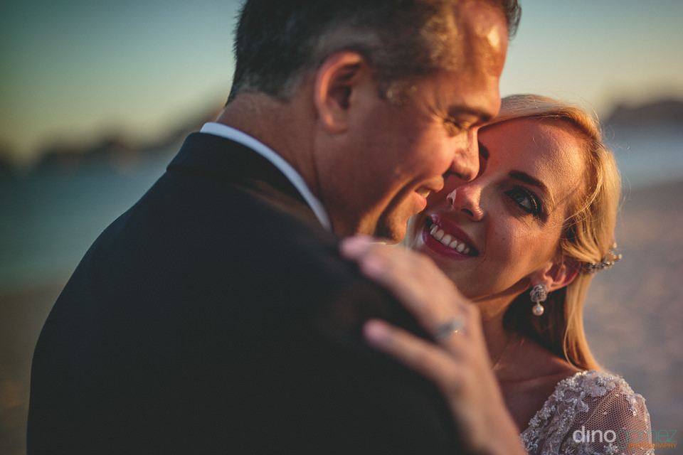 happy bride and groom smile at each other at sunset on the beach