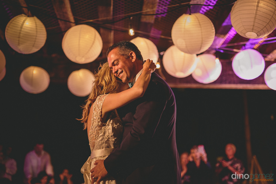 newlyweds dance as wedding guests watch happily
