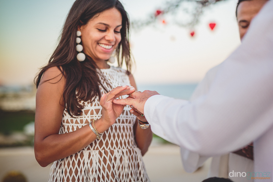 bride puts ring on grooms finger at destination package wedding