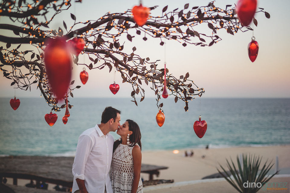 kissing on the beach at cabo destination wedding photographed by