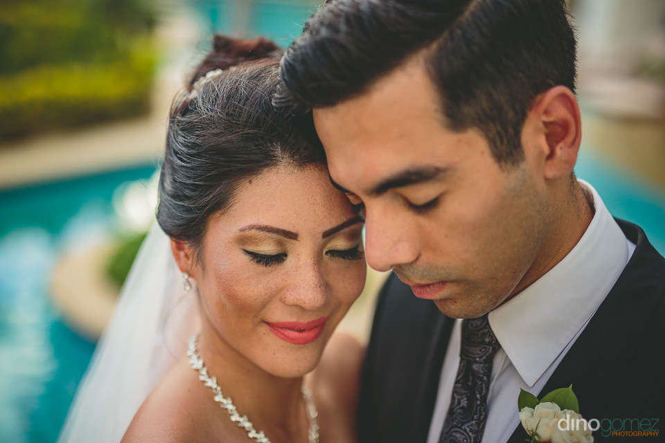 closeup photo of attractive newlyweds on wedding day in cabo san