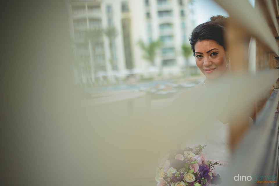 photo of newlywed bride taken through blinds at mexico resort