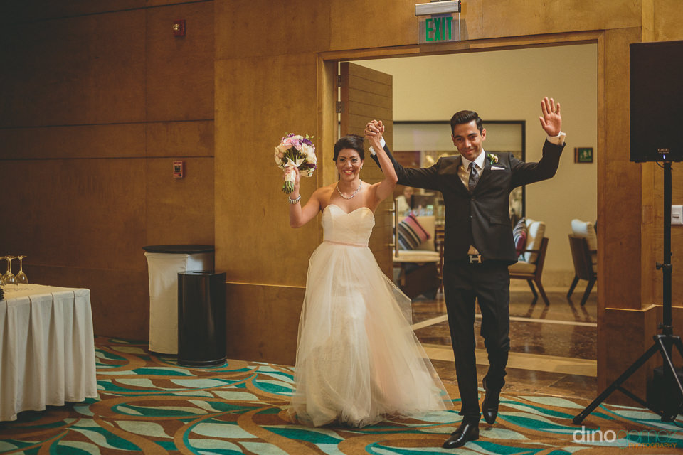 newlywed couple enter wedding dinner together and guests celebra