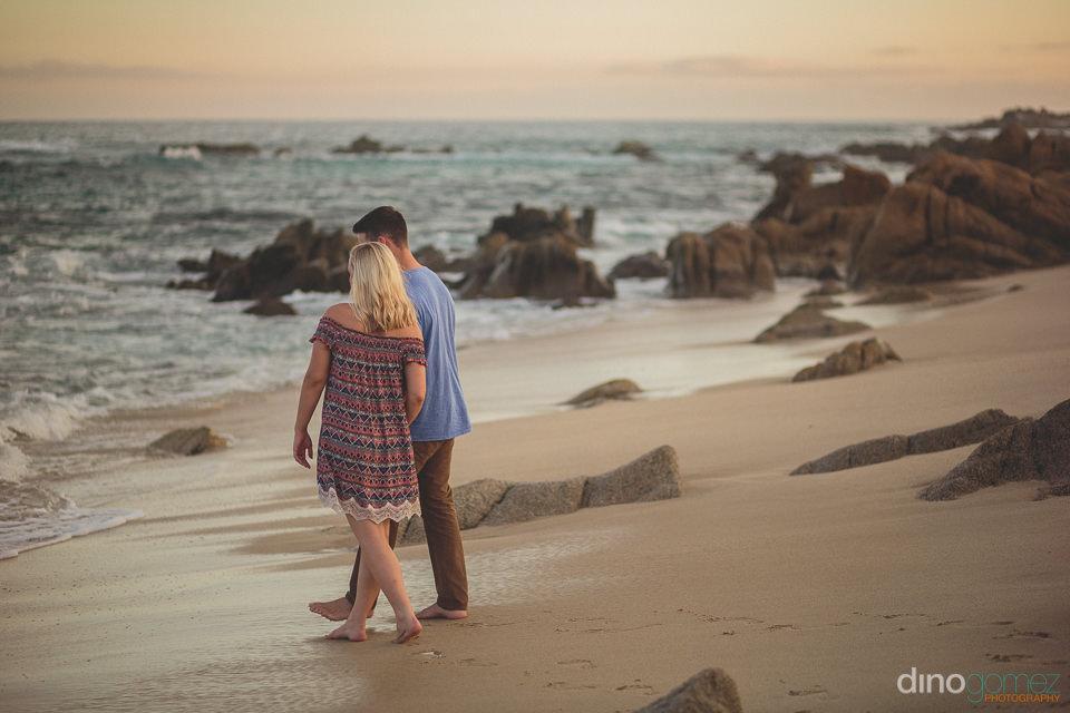 newlyweds walk on rocky cabo mexico beach at sunset wedding phot